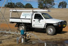 A white truck parked outside a field used for testing and servicing of solar products
