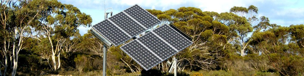 A solar tracker with 6 sun ray solar collectors planted in an open area with trees in the background