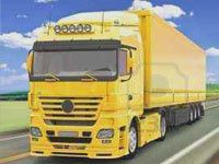 An image showing a yellow container truck on a road with grass fields and blue sky in background